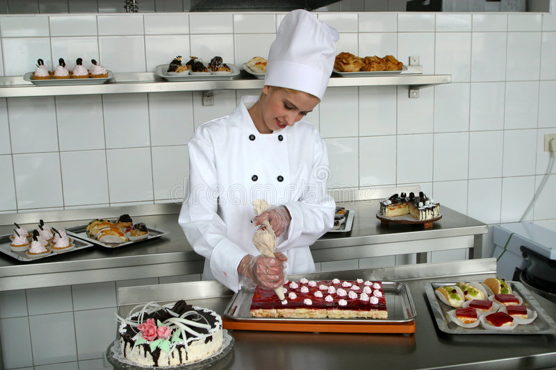 Young girl baking cakes. In kitchen royalty free stock photography