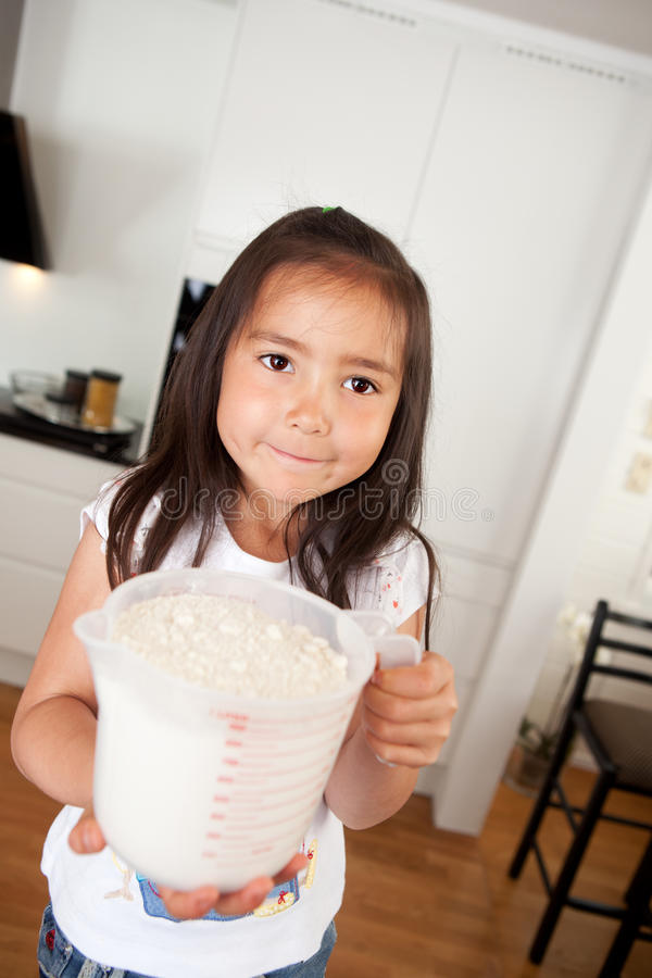 Young Girl Baking Measuring Cup of Flour royalty free stock photography