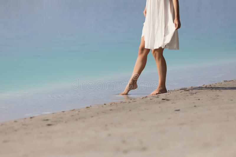 Young girl barefoot stands in the sand stock image
