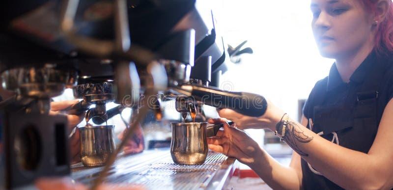 Young girl Barista prepares coffee in pub, bar. Espresso machine making coffee in pub, bar royalty free stock image
