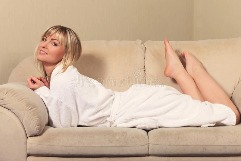 Girl in a bathrobe on the couch. Young girl in a bathrobe on the couch stock images