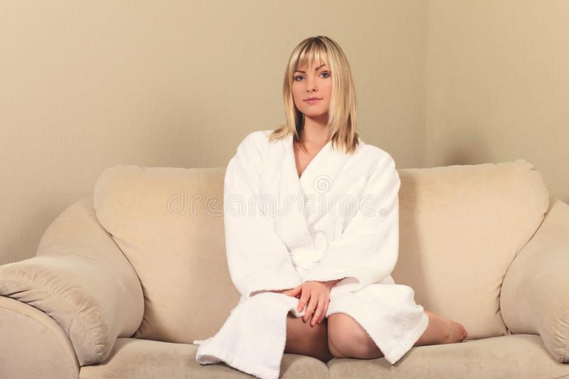 Girl in a bathrobe on the couch. Young girl in a bathrobe on the couch stock photo