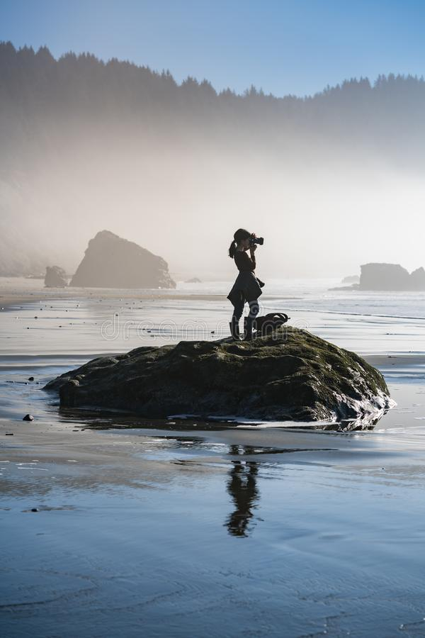 Young girl on beach taking photos of Oregon coast. This is a photograph of a young girl standing on a beach rock and taking photo of Oregon coast stock photography