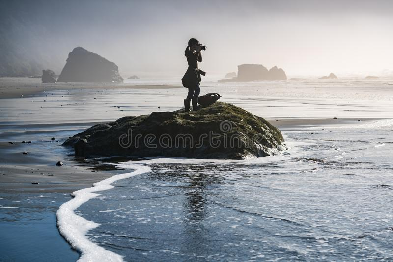 Young girl on beach taking photos of Pacific Ocean in Oregon coast. This is a photograph of a young girl standing on a beach rock and taking photo of Oregon stock photos