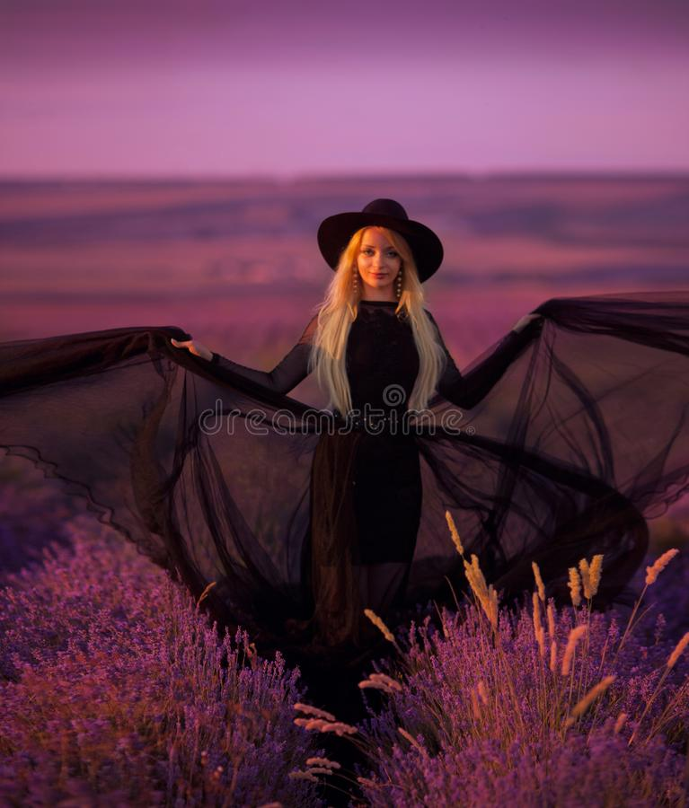 Beautiful young girl walks in a field of lavender stock image
