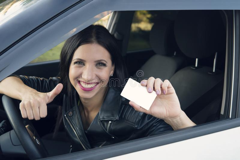 Young girl with beautiful smile sitting in white car showing an empty white card and thumbs up hand sign. Woman has got driving. License and is very happy royalty free stock image