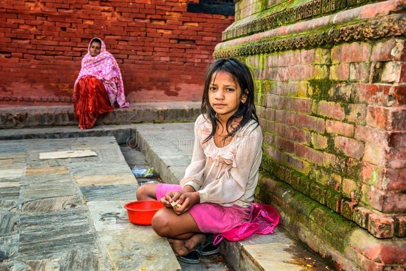 Young girl begging at Pashupatinath Temple complex in Kathmandu, Nepal. KATHMANDU, NEPAL - OCTOBER 20, 2015 : Young girl begging for alms at Pashupatinath Temple royalty free stock photo