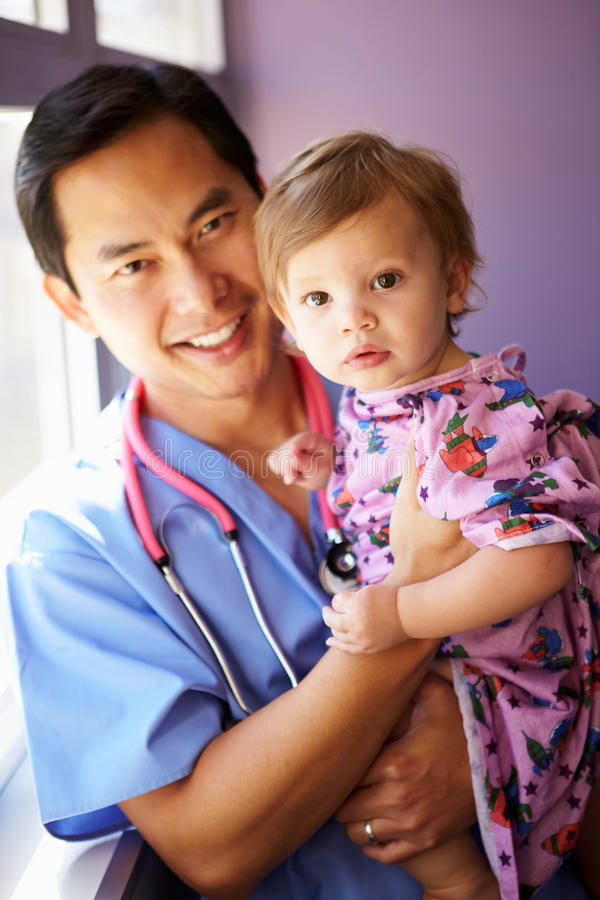Young Girl Being Held By Male Pediatric Nurse. Smiling At Camera royalty free stock photos