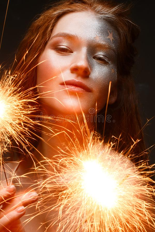 A young girl with bengal lights and red hair. A beautiful model with shining skin and glitter make-up. New Year`s and a holiday im stock photography