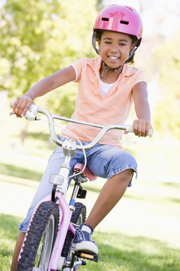 Young girl on bicycle outdoors smiling stock photography