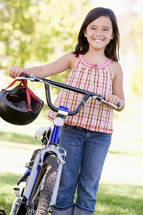 Young girl with bicycle outdoors smiling royalty free stock images