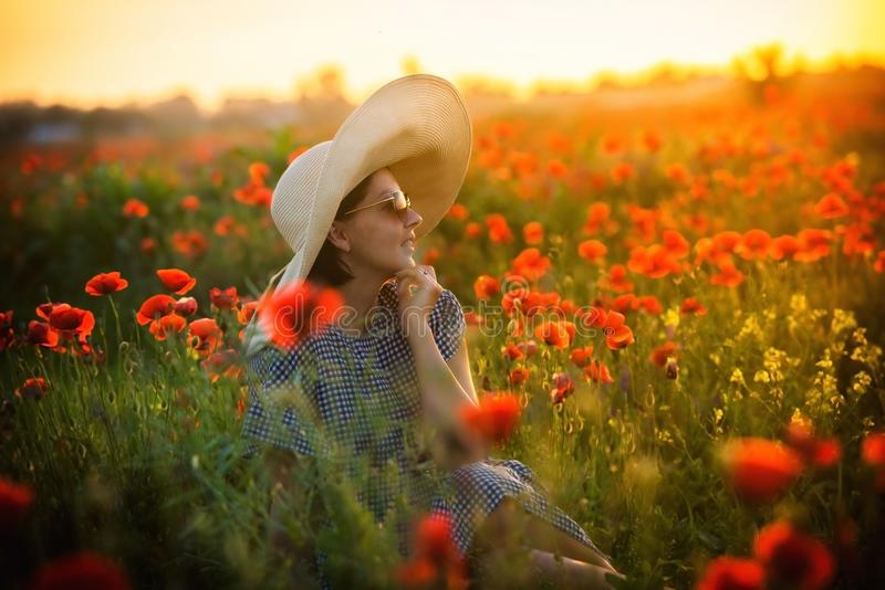 Young girl in a big hat sitting on a poppy field in sunset stock image