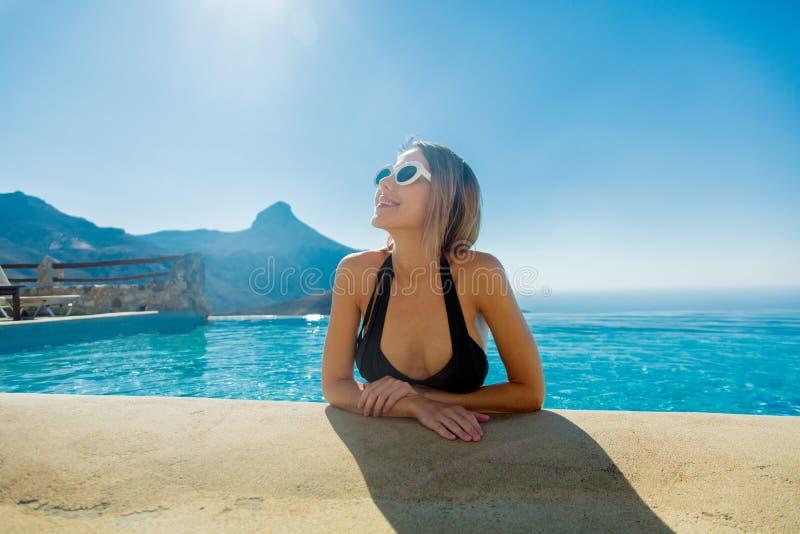 Young girl in bikini and sunglasses in a pool stock photo