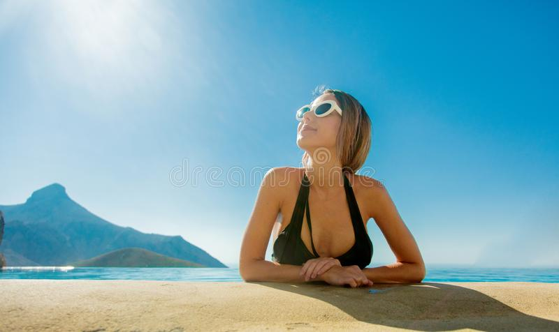 Young girl in bikini and sunglasses in a pool stock images
