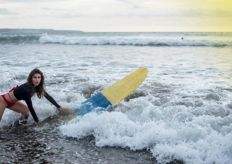 Young girl in bikini - surfer with surf board dive underwater with fun under big ocean wave. Family lifestyle, people stock photo
