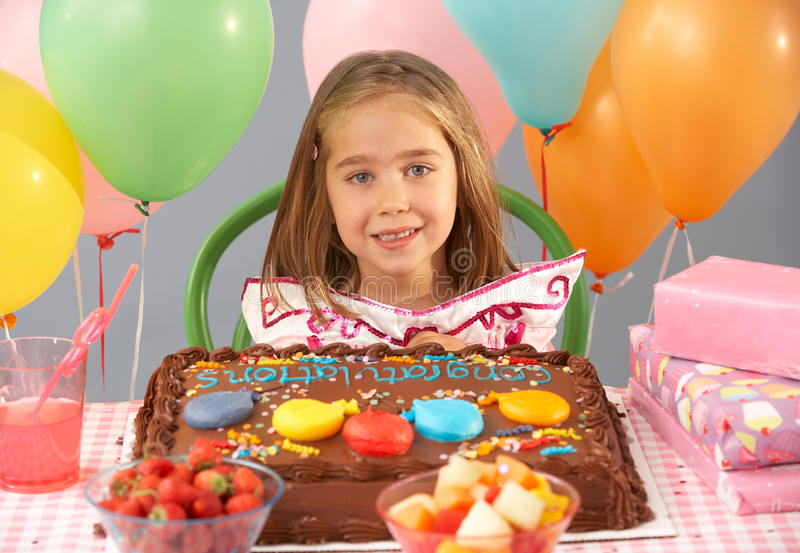 Young girl with birthday cake and gifts. At party stock images