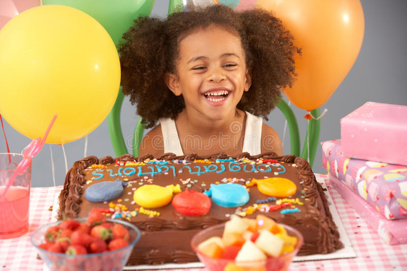 Young girl with birthday cake and gifts at party. Laughing royalty free stock image