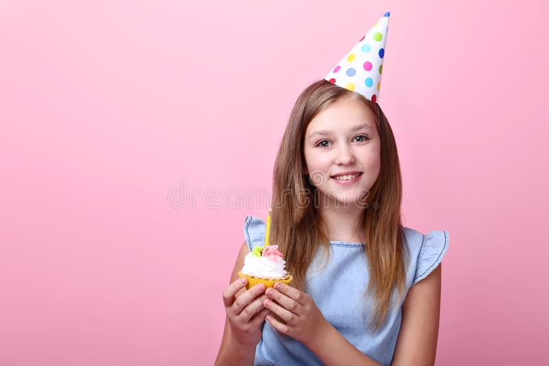 Young girl in birthday hat. Cute young girl in birthday hat holding cupcake on pink background stock photos