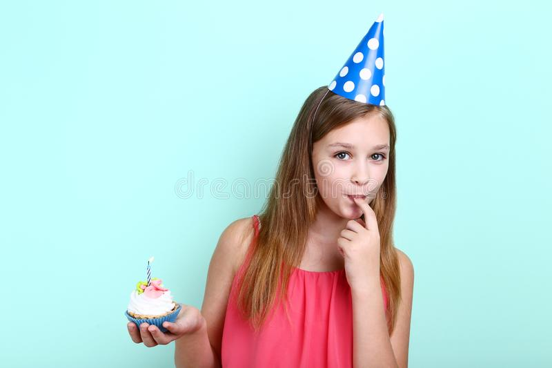 Young girl in birthday hat. Holding cupcake with candle on mint background royalty free stock photos