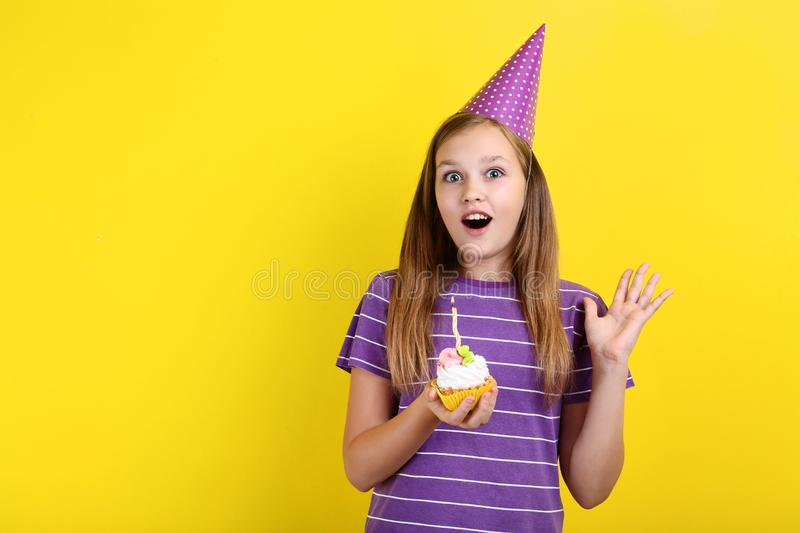 Young girl in birthday hat. Holding cupcake with candle on yellow background royalty free stock image