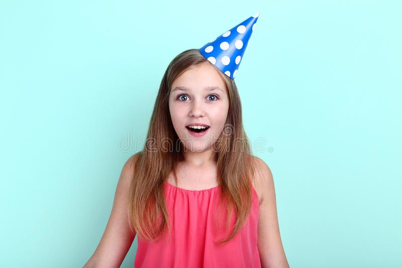 Girl in birthday hat. Young girl in birthday hat on mint background stock photography