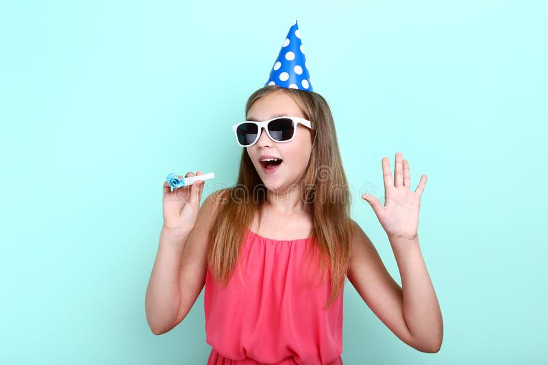 Young girl in birthday hat. With sunglasses and whistle on mint background stock photo