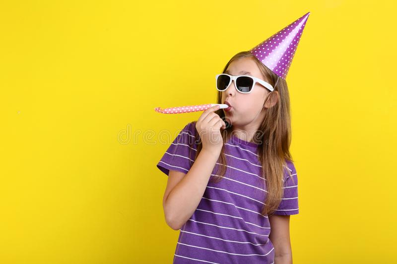 Girl in birthday hat with sunglasses. Young girl in birthday hat with sunglasses and whistle on yellow background royalty free stock photos
