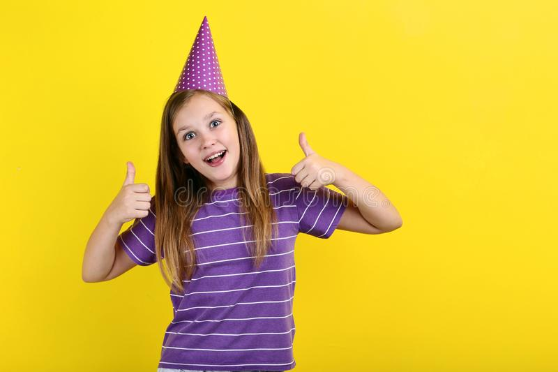 Girl in birthday hat. Young girl in birthday hat on yellow background royalty free stock photography