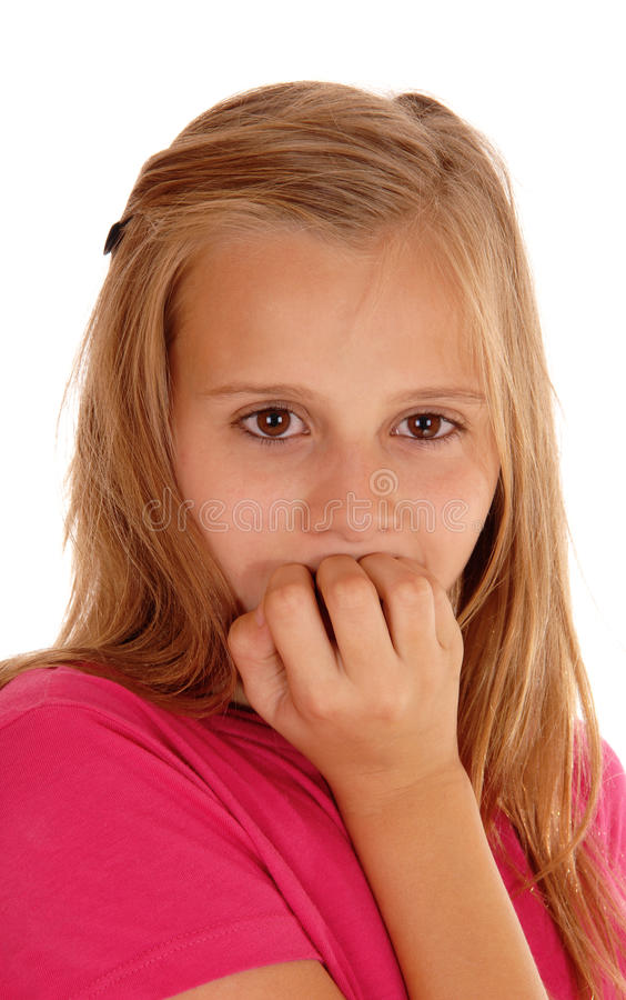 Young girl biting her fingernails. A scaret young girl in a pink sweater in a closeup picture biting her fingernails, isolated for white background stock photo
