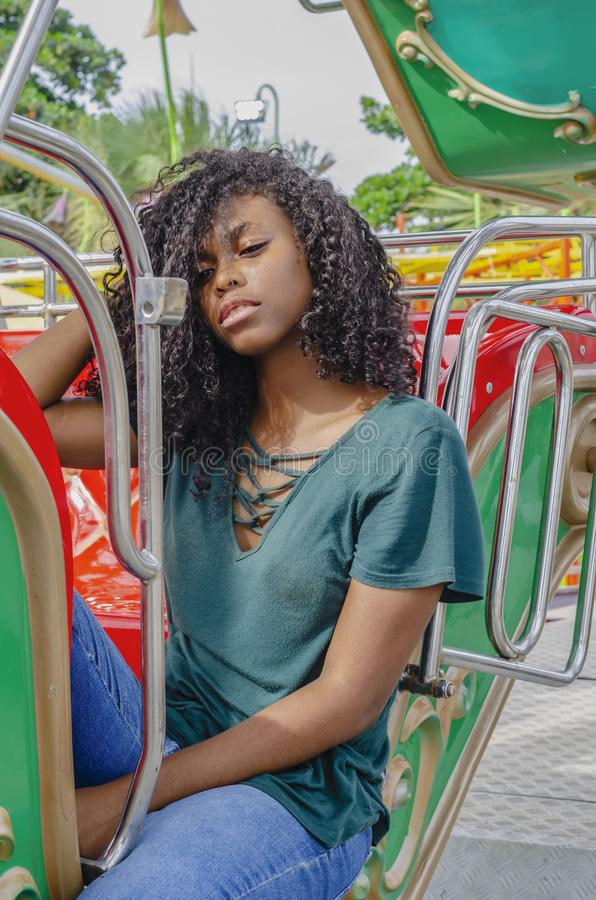 Young girl of black color, laughing hair in ferris wheel, sitting enjoying a summer day. Lifestyle portrait royalty free stock photo