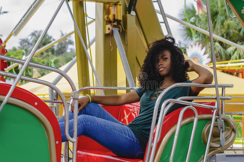Young girl of black color, laughing hair in ferris wheel, sitting enjoying a summer day. Lifestyle portrait stock photo