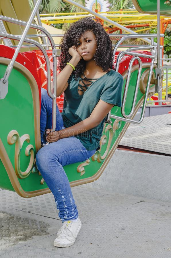 Young girl of black color, laughing hair in ferris wheel, sitting enjoying a summer day. Lifestyle portrait royalty free stock images