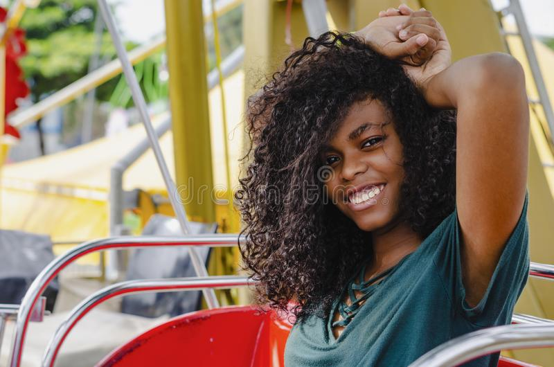 Young girl of black color, laughing hair in ferris wheel, sitting enjoying a summer day. Lifestyle portrait stock image