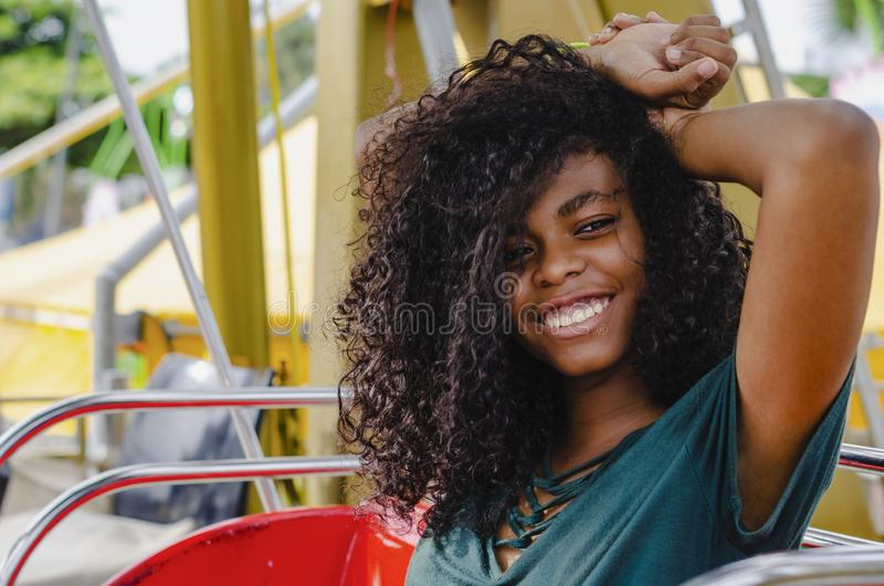 Young girl of black color, laughing hair in ferris wheel, sitting enjoying a summer day. Lifestyle portrait stock images