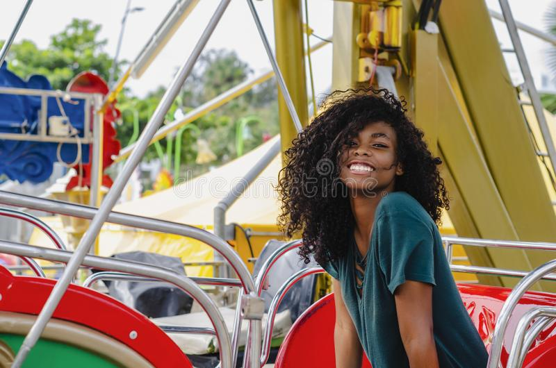 Young girl of black color, laughing hair in ferris wheel, sitting enjoying a summer day. Lifestyle portrait stock photos