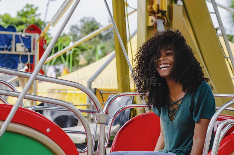 Young girl of black color, laughing hair in ferris wheel, sitting enjoying a summer day. Lifestyle portrait stock photography