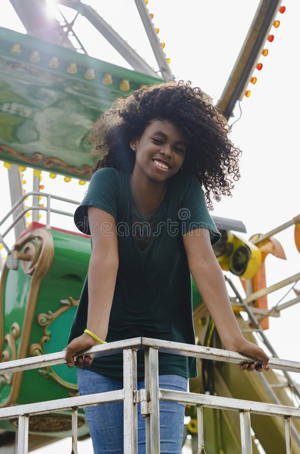 Young girl of black color, laughing hair in ferris wheel, sitting enjoying a summer day. Lifestyle portrait royalty free stock image