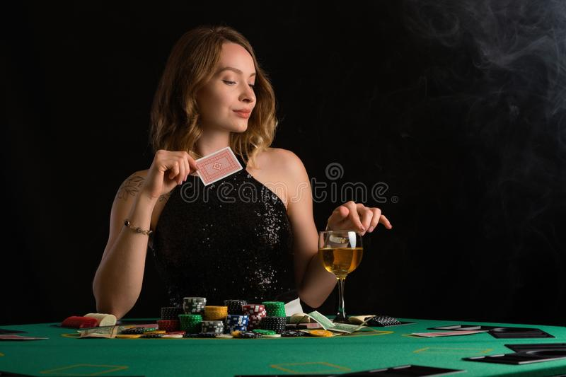 A young girl in a black evening dress plays poker in a casino. on a black background, horizontal photo.  stock image