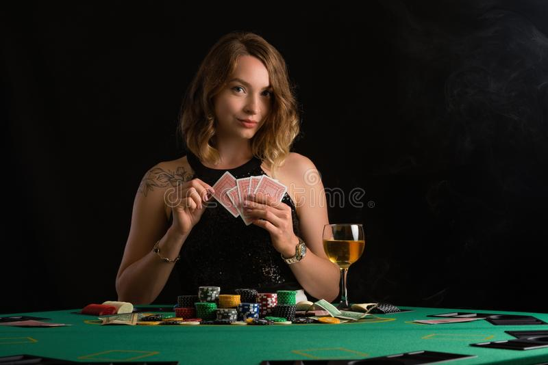 A young girl in a black evening dress plays poker in a casino. on a black background, horizontal photo.  stock photo