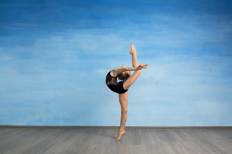 A young girl in a black gymnastic swimsuit gymnast makes an exercise standing backward and legs in semi splits on a blue backgroun stock photos