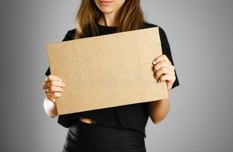 A young girl in a black t-shirt holding a piece of cardboard. Pr stock photos