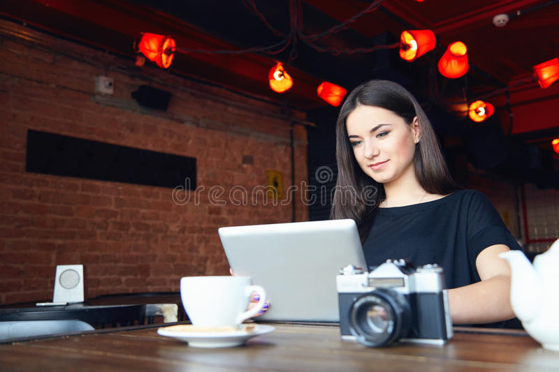Young girl bloger freelancer photographer working on laptop in cafe stock images