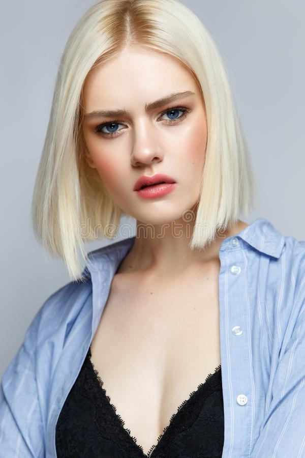 A young girl with blond hair and in a blue shirt with a gentle make-up and blush. Beautiful model with shining skin. A young girl with blond hair and in a blue stock photo