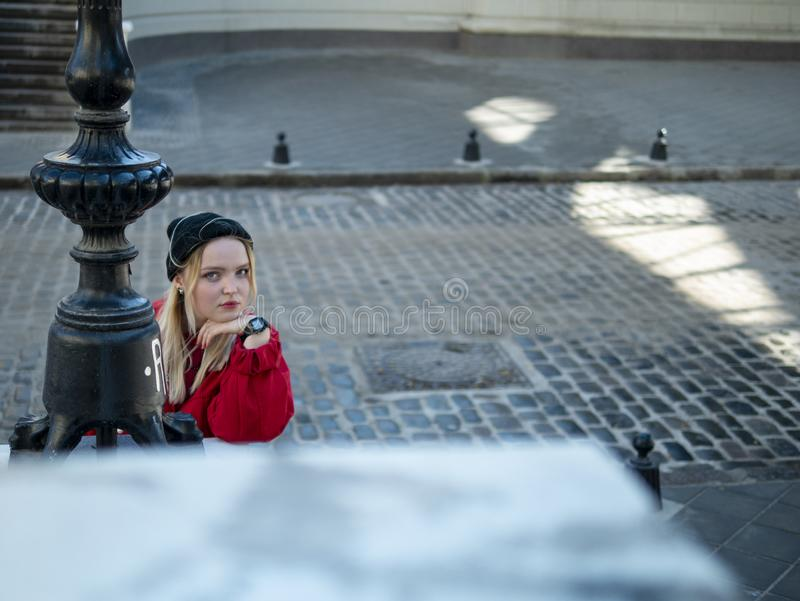 A young girl blonde in a knitted black hat and a red jacket stands near the lantern on the background of a paving stone.  royalty free stock photo