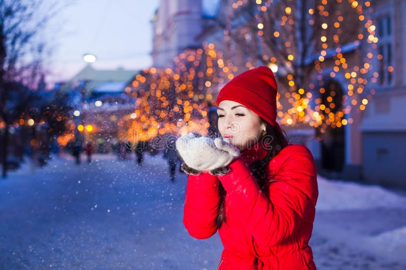 Young girl blowing away snow from mittens stock photo