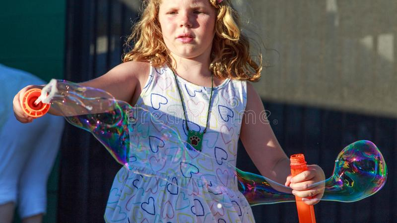 Young girl blowing big bubbles stock photo