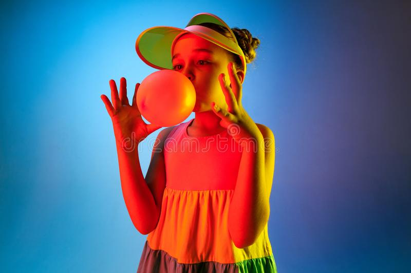 Young girl blowing bubble gum. Happy teen girl standing over trendy blue neon studio background. Beautiful female portrait. Young satisfy girl. Human emotions stock photography