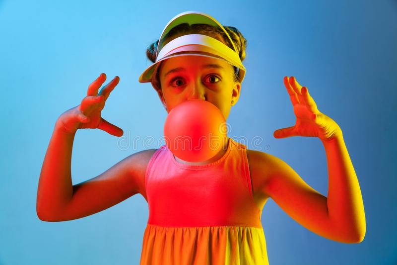 Young girl blowing bubble gum. Happy teen girl standing over trendy blue neon studio background. Beautiful female portrait. Young satisfy girl. Human emotions stock photos