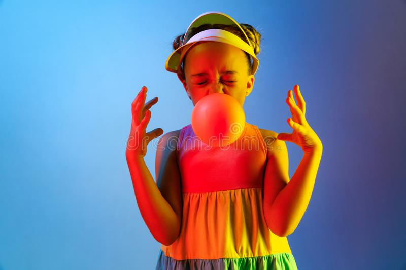 Young girl blowing bubble gum. Happy teen girl standing over trendy blue neon studio background. Beautiful female portrait. Young satisfy girl. Human emotions royalty free stock images