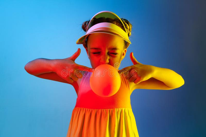 Young girl blowing bubble gum. Happy teen girl standing over trendy blue neon studio background. Beautiful female portrait. Young satisfy girl. Human emotions stock photo